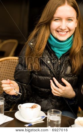 Beautiful Smiling Girl With A Cup Of Cappuccino In A Parisian Street Cafe