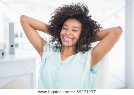 Happy businesswoman relaxing in swivel chair in her office