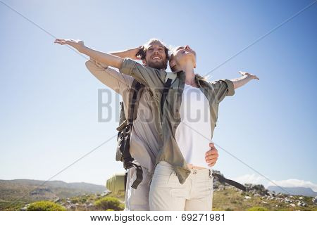 Hiking couple standing on mountain terrain admiring the view on a sunny day