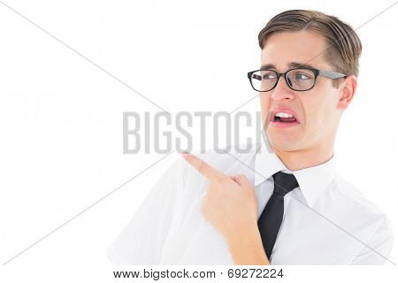 Geeky young hipster pointing with disgust on white background
