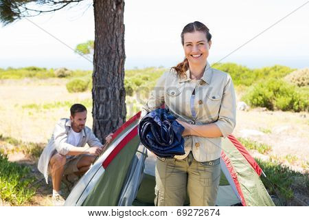 Outdoorsy couple setting up camp in the countryside on a sunny day