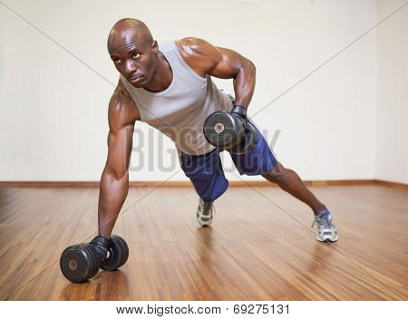 Full length of a muscular man doing push ups with dumbbells in gym