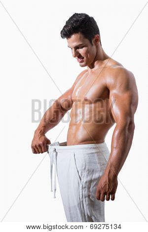 Side view of a muscular man in an over sized pants against white background