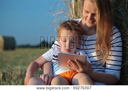 Mother and son with pad sitting by hay roll in the field