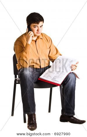 Young Man Sitting On A Chair Talking On The Phone And Examine Documents In The Red Folder