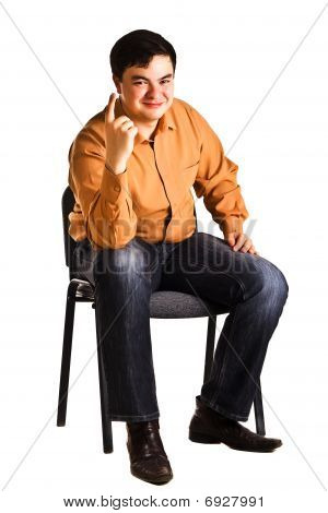 Young Man Sitting On A Chair Shows The Finger