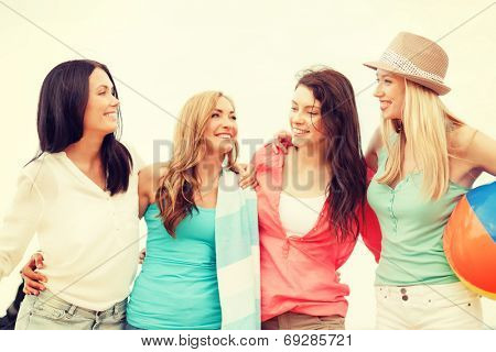 summer holidays, vacation and beach activities concept - smiling girls with ball and towel on the beach