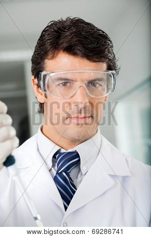 Portrait of confident male scientist in protective eyewear at laboratory
