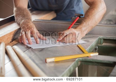 Cropped image of carpenter working on blueprint at tablesaw in workshop