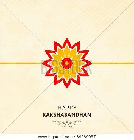 Beautiful rakhi on beige background for Happy Raksha Bandhan festival celebrations.