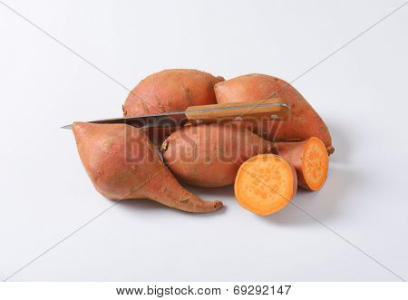 batata sweet potatoes and kitchen knife on white background