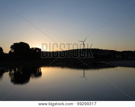 Sunsets Over Stream Leading To Beach With Windmill Visible