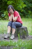 stock photo of pain-tree  - older woman sitting on a tree stump and looking sad - JPG