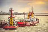 image of freightliner  - Red Boats in Sea Port transport strait of Kerch in Crimea with sunset sky on background - JPG