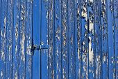 image of hasp  - background pattern and texture of an old wooden door with weathered blue paint and hasp and staple lock - JPG