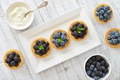 stock photo of tarts  - Delicious mini tart with fresh blackberries and blueberries on wooden background - JPG