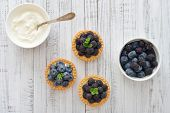 foto of tarts  - Delicious mini tart with fresh blackberries and blueberries on wooden background - JPG