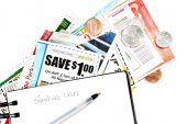 stock photo of grocery-shopping  - shopping list with coupons and American coins - JPG