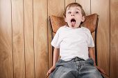 stock photo of misbehaving  - Young boy sitting in a chair with mouth open wide - JPG