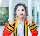 stock photo of polite girl  - Graduate Thai college girl in academic gown is holding poles and smiling happily for the moment