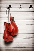 stock photo of knockout  - Boxing gloves hanging on wooden wall  - JPG