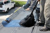image of tar  - Unidentifiable workers use  - JPG