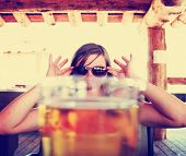 stock photo of draft  - woman peeking over a fresh draft beer toned with a vintage retro style instagram filter - JPG