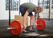 stock photo of jerks  - Full length of fit young man picking barbell in box - JPG