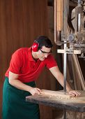 stock photo of workbench  - Young male carpenter cutting wood with bandsaw in workshop - JPG