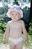 image of pouting  - Summer little girl in a bathing suit standing on the beach near the bushes and pouted - JPG