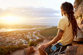 image of dreadlock  - A man in dreadlocks on a mountain looking at the view with copyspace - JPG
