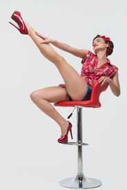 stock photo of halter-top  - Glamorous young smiling girl wearing great red halter top blue shorts sitting on the red stool showing us her great legs - JPG