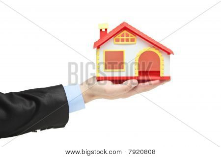Real estate agent holding a model house in a hand