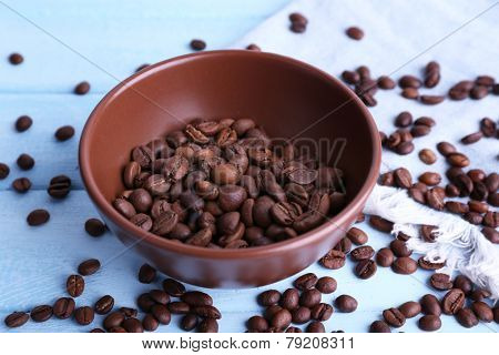 Bowl of ground coffee and coffee beans on blue wooden background with jeans material