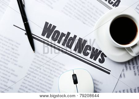 On-line news concept. Computer mouse, cup of coffee and newspaper, close-up