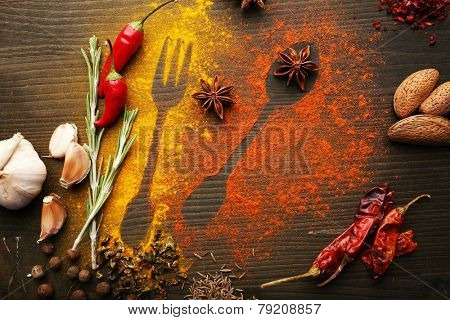 Spices on table with cutlery silhouette, close-up