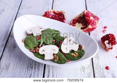 Fresh salad with greens, garnet and spices on plate on table close-up