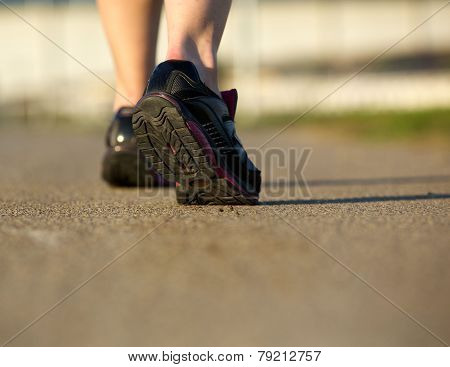 Rear View Of A Woman Walking In Gym Shoes On A Path