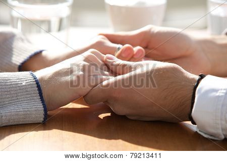 Male And Female Holding Hands Over Table