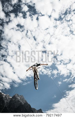 stunt dirt biker with hands free high in the cloudy sky and mountains