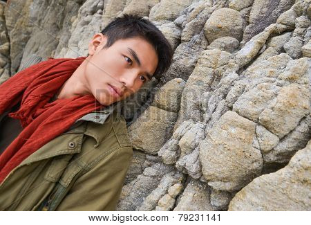 young man in scarf with coat n a rock at beach background