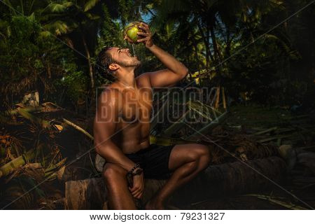 Young man on vacations sitting a palm tree and rinking coconut