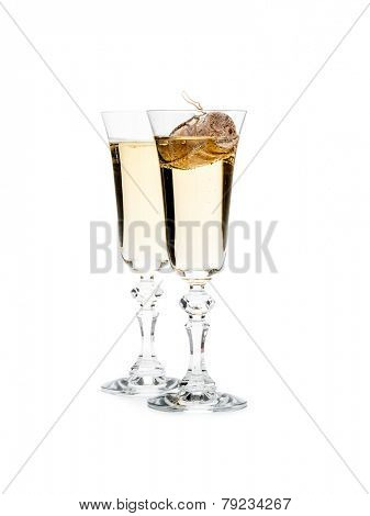 Two champagne glasses with champagne cork floating in one glass shot on white