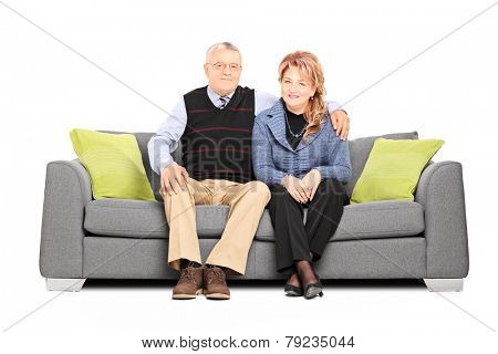 Lovely mature couple posing seated on sofa isolated on white background
