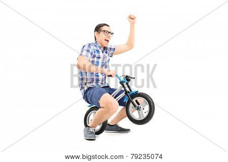 Crazy young man riding a small bike isolated on white background
