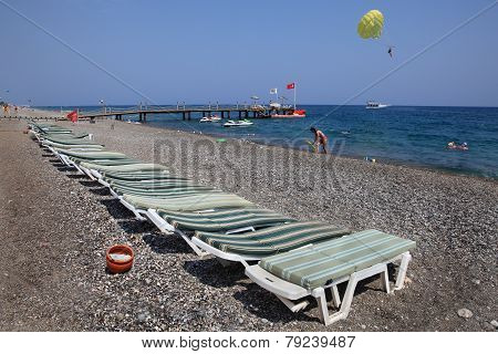 Sunbeds On Pebbled Beach Of Mediterranean Resort.