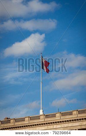 Flag Of France Fluttering Under A Serene Blue Sky