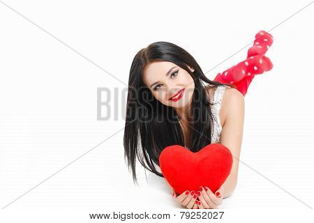 Beautiful brunette lying cross-legged like the tail of a fish, with a red heart in his hand.