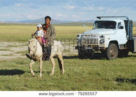Mongolian man rides on horseback with kids, Harhorin, Mongolia.