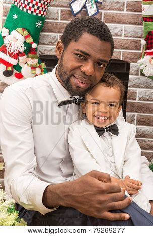 Happy Black Father And Baby Boy Cuddling By Fireplace. Christmas And New Year